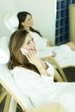 2 женщины в купальных халатах ослабляя в курорте Стоковое Фото