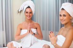 2 женщины в купальных халатах при друзья полотенец ослабляя домашний курорт Стоковая Фотография RF