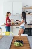 2 женщины в кухне варя говорить подготавливающ еду стоковая фотография