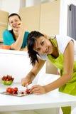 2 женщины в кухне варя и есть счастливые Стоковая Фотография