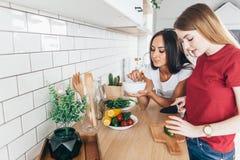 2 женщины в кухне подготавливают салат Стоковые Фотографии RF