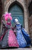 2 женщины в масках и богато украшенных голубых и розовых костюмах стоя перед старой голубой дверью в Венеции во время масленицы Стоковое фото RF