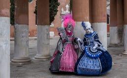 2 женщины в масках и богато украшенных голубых и розовых костюмы на масленице Венеции Стоковые Изображения