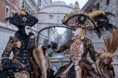 Женщины в масках и костюмы, с мостом вздохов позади, на масленице Венеции Стоковая Фотография RF