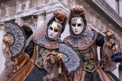 2 женщины в масках и костюм, при украшенные вентиляторы, стоя перед сводами на метках St придают квадратную форму во время маслен Стоковое Изображение RF