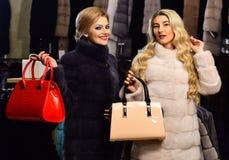 Женщины в меховых шыбах с сумками в мехе ходят по магазинам Стоковые Изображения
