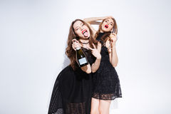 Женщины в ноче одевают выпивая шампанское и tonque показывать Стоковая Фотография