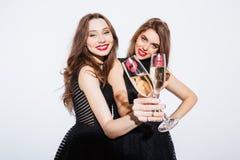 2 женщины в ноче одевают держать стеклянный с шампанским Стоковая Фотография RF