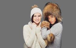 2 женщины в одеждах зимы на белой предпосылке Стоковые Фото
