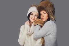 2 женщины в одеждах зимы на белой предпосылке Стоковая Фотография