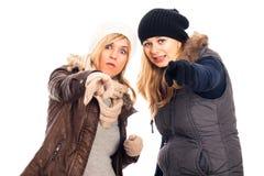 Женщины в одеждах зимы указывая на вас Стоковые Изображения