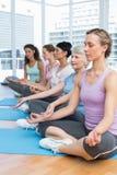 Женщины в лотосе представляют при глаза закрытые на студии фитнеса Стоковые Изображения RF