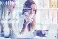 2 женщины в офисе, gaphs и карте Стоковое фото RF