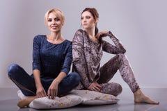 2 женщины в пижамах сидят на подушках на серой предпосылке стоковое фото