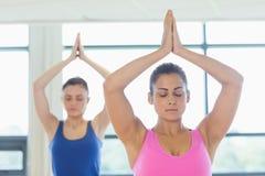2 женщины в положении Namaste с глазами закрыли на студии фитнеса Стоковая Фотография