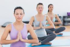 Женщины в положении Namaste с глазами закрыли на студии фитнеса Стоковая Фотография