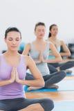 Женщины в положении Namaste с глазами закрыли на студии фитнеса Стоковое Изображение RF
