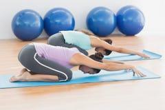 2 женщины в представлении раздумья на студию фитнеса Стоковое фото RF