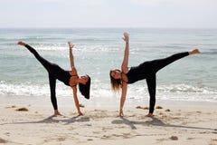 Женщины в представлениях йоги на запас пляжа отображают Стоковое Изображение