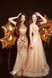 2 женщины в платье моды, торжестве партии Брюнет дублирует gi Стоковые Фото