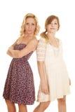 2 женщины в платьях спина к спине серьезных Стоковая Фотография