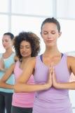 Женщины в раздумье представляют при глаза закрытые на студии фитнеса Стоковое Изображение RF