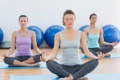 Женщины в раздумье представляют при глаза закрытые на студии фитнеса Стоковые Изображения