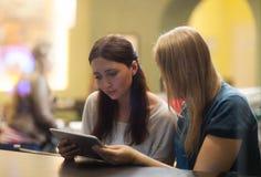 2 женщины в ресторане используя электронное Стоковое Изображение RF