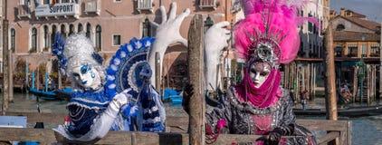 2 женщины в розовых и голубых костюмах с вентиляторами и богато украшенных покрашенных масках перед гостиницой Sagredo на Венеции Стоковые Изображения