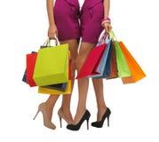 2 женщины в розовых платьях с хозяйственными сумками Стоковая Фотография