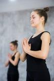 2 женщины в спортзале классифицируют, тренировка релаксации или занятия йогой Стоковое фото RF
