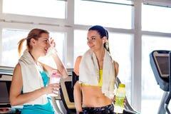 2 женщины в спортзале с бутылками с водой и полотенцами Стоковая Фотография
