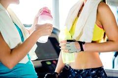 2 женщины в спортзале с бутылками с водой и полотенцами Стоковое Изображение