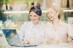 2 женщины в столовой с Coffe и компьтер-книжкой Стоковое фото RF