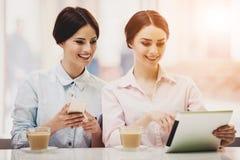 2 женщины в столовой с Coffe и таблеткой Стоковое Изображение RF