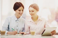 2 женщины в столовой с Coffe и таблеткой Стоковое фото RF