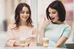 2 женщины в столовой с Coffe и Smartphone Стоковая Фотография