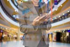 Женщины в торговом центре используя мобильный телефон Стоковое Изображение