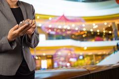 Женщины в торговом центре используя мобильный телефон Стоковые Фотографии RF