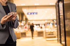 Женщины в торговом центре используя мобильный телефон Стоковые Фото