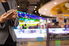 Женщины в торговом центре используя мобильный телефон Стоковое фото RF