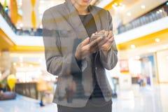 Женщины в торговом центре используя мобильный телефон Стоковая Фотография