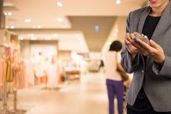 Женщины в торговом центре используя мобильный телефон Стоковые Изображения RF
