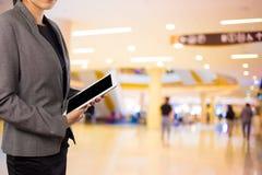 Женщины в торговом центре используя передвижной ПК таблетки Стоковое Изображение