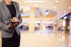 Женщины в торговом центре используя передвижной ПК таблетки Стоковые Фото