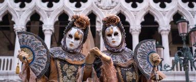 2 женщины в традиционном костюме и покрашенных масках, при украшенные вентиляторы, стоя перед дворцом дожей во время Венеции Carn Стоковое Изображение RF