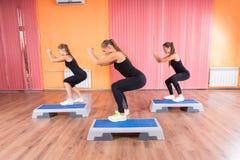 Женщины в тренировке сидеть на корточках используя платформы Стоковое Изображение