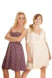 2 женщины в улыбке стороны платьев спина к спине Стоковые Изображения RF