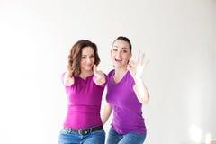 2 женщины в фиолетовых пальцах выставки одежд Стоковые Изображения RF