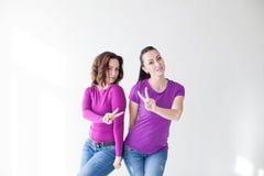 2 женщины в фиолетовых пальцах выставки одежд Стоковые Фото